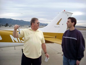 Pilot Nevens is checking the fuel in the plane before takeoff!  Dave Cole seems very interested in this part.